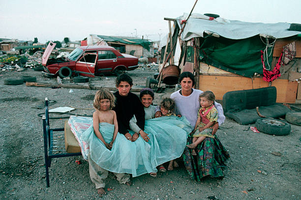 A Roma woman and her daughters sit on an old bed near dilapidated shacks and broken down cars. The Roma, or Gypsies, are travelling people and are often mistrusted by the societies in which they live. Gypsies are now concentraited in Southern Europe, though there are an estimated 9-12 Million Roma worldwide.   (Photo by Peter Turnley/Corbis/VCG via Getty Images)